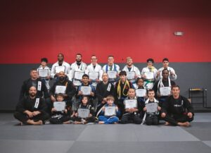 Group of martial arts students and instructors posing with certificates