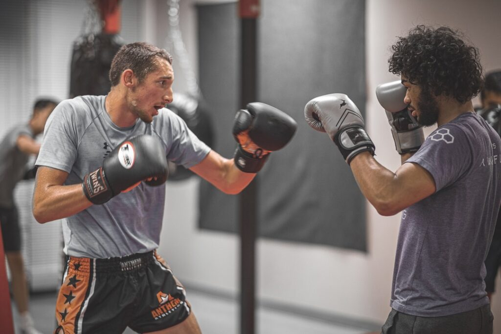 Two men boxing each other in a class