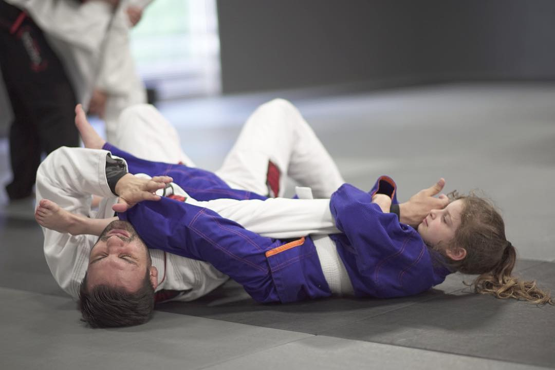 Young girl grappling with a man on the floor in martial arts uniforms