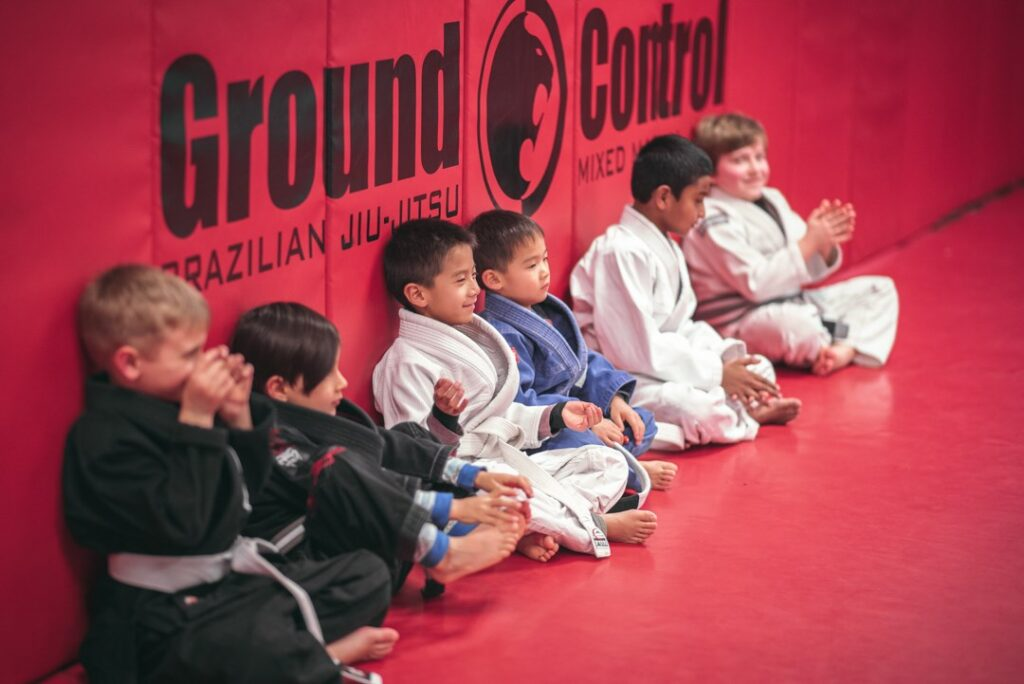 Kids sitting against the wall in a martial arts class