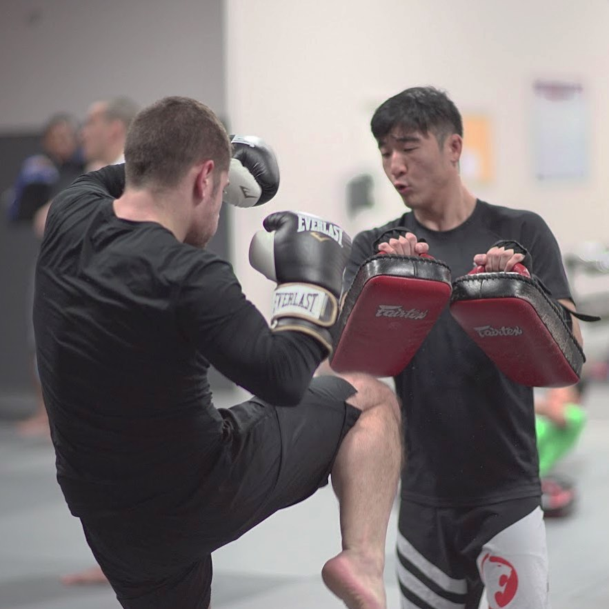Man practicing muay thai with another man holding strike pads