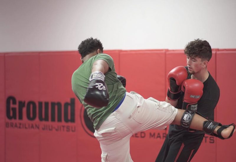 Man kicking another man in the side with boxing gloves on
